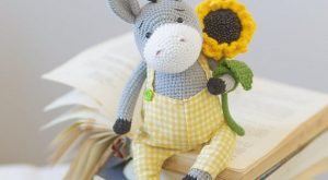 Soft crocheted cute toy donkey in plaid yellow pants with a sunflower beautiful gift…